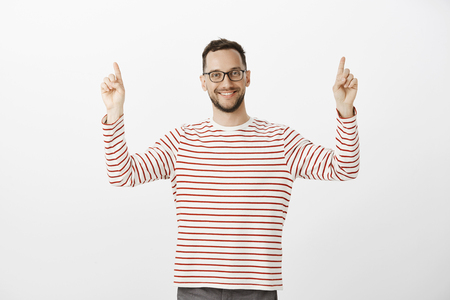 Portrait of friendly good-looking male neighbour in trendy glasses, raising index fingers and pointing up, smiling broadly, standing against gray background pleased and happy. Stock Photo