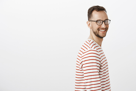 Profile portrait of carefree friendly-looking caucasian guy with beard in black glasses, turning and smiling at camera with positive attitude, having fun and being relaxed over gray wall