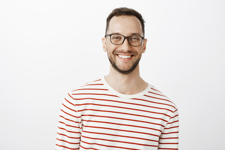 Waist-up shot of relaxed good-looking positive guy in glasses, smiling broadly and gazing at camera while talking with friend, standing against gray background, discussing interesting topic Stock Photo