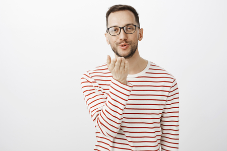 Sending kisses to you. Portrait of cute good-looking gay man in glasses, holding palm near mouth and blowing mwah at camera with slight smile, showing simpathy to boyfriend over gray wall Stock Photo