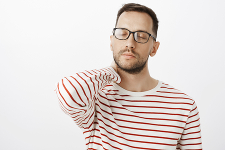 Studio shot of calm tired busy guy in black trendy glasses, closing eyes and massaging back of neck, feeling tired after working day, relaxing and having break, standing over gray background Stock Photo
