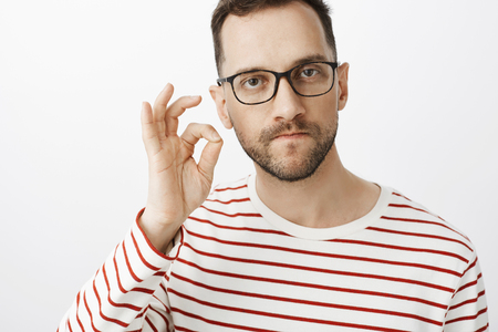 Studio shot of serious pissed off angry man in glasses, zipping mouth with finger gesture and threatening person to keep silent or shut up, demanding not spread any rumors over gray background