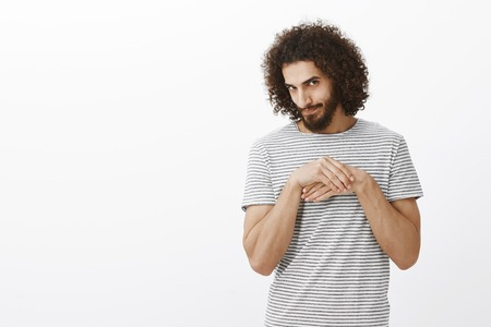 Portrait of sneaky good-looking curly-haired man with beard, rubbing palms near chest, looking from under forehead with curious expression, having bad intentions and ideas, standing over gray wall