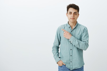 Portrait of calm confident good-looking boyfriend in shirt and jeans, holding hand in pocket and pointing at upper left corner with slight smirk, being self-assured and pleased over gray wall
