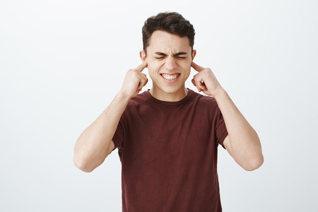 Indoor shot of displeased european male model in casual t-shirt, clenching teeth and closing eyes from annoyance, covering ears with index fingers, hearing hateful song or loud disturbing noise Stock Photo