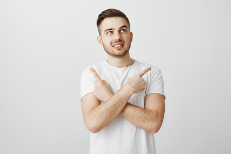 Unsure worried guy feeling nervous making wrong decision standing intense over gray background in white t-shirt crossing hands on chest pointing left and right being in doubts and hesitating