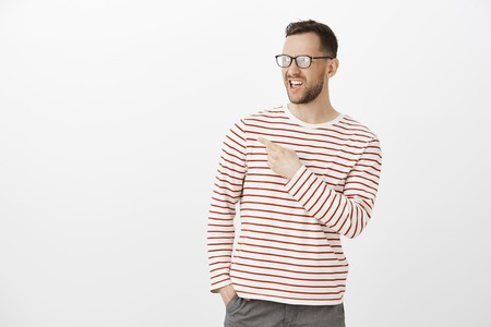 Disgusted displeased adult man in glasses, spreading rumor or discussing person who stands back, pointing at upper left corner with disappointed expression. Gossip concept