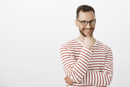 Indoor shot of playful good-looking gay guy in black glasses, smiling with intrigued expression, having some interesting desire or intension, touching beard and gazing at camera, having nasty thought Stock Photo