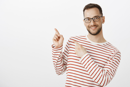 Cute tender adult male gay model in glasses, pointing at upper left corner with finger gun gestures and smiling with pleased friendly expression, showing lgbt place to friend over gray wall Reklamní fotografie