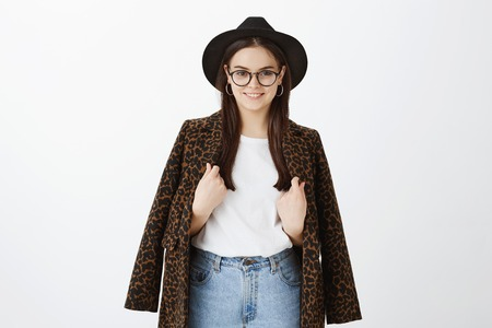 Horizontal shot of stylish feminine fashion blogger in trendy hat, glasses and coat with leopard print over t-shirt, touching clothes and smiling broadly while taking interview from celebrity Stockfoto