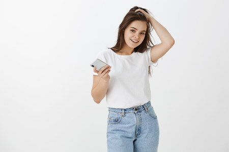 Joyful carefree female student in stylish jeans and t-shirt, touching hair sensually and smiling while gazing joyfully at camera, holding smartphone, asking coworker help with new gadget
