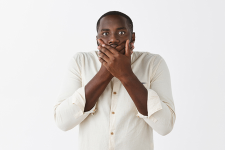 Portrait of troubled and worried shocked dark-skinned male with short haircut in white shirt, covering mouth with both palms, staring nervous at camera Stock Photo