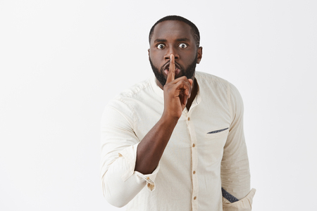 Pissed angry african american guy with beard in white shirt, bending towards camera with scary expression, saying shh while showing shush gesture with index finger over mouth