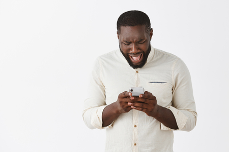 Disappointed upset dark-skinned male model in white shirt, frowning and complaining while reading disappointing message in smartphone, holding device with both hands and looking at screen