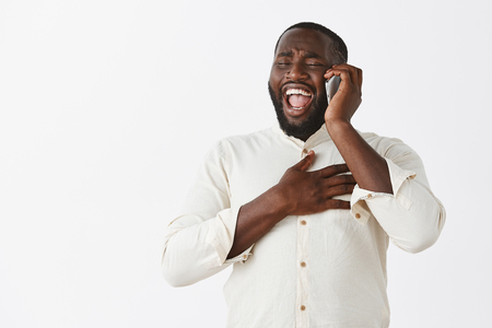 Amused happy and joyful attractive African American laughing out loud from amazing story told by friend via smartphone, chuckling, bending backwards from joy, touching chest Stock Photo