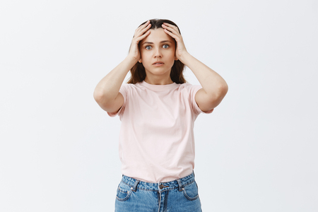 Woman facing troublesome situation being worried and tired. Portrait of stunned attractive young female studen in pink t-shirt holding hands on head and staring worried at camera