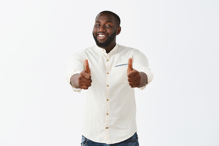 Studio shot of pleased good-looking crafty male african american chef in white shirt, smiling broadly from satisfaction, showing thumbs up at camera, liking new meal and suggesting everyone try it Foto de archivo