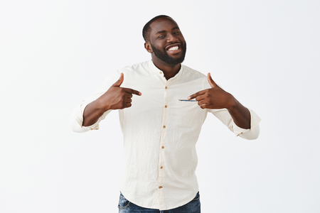 I am best. Portrait of good-looking confident and happy african american bearded guy with short haircut, pointing at himself with proud and pleased expression, standing over gray background 写真素材