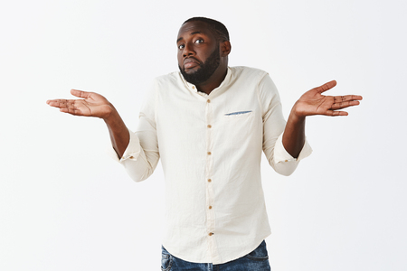 Bro have no idea. Portrait of clueless handsome African American in white shirt and jeans, shrugging with both hands aside, pursing lips and pouting, being unaware and uncertain in answer