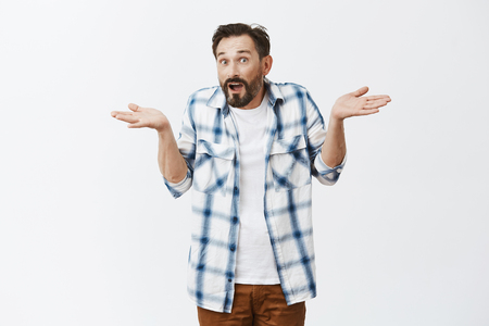 How should I know. Unaware confused adult guy with beard and moustache in casual checked shirt over t-shirt, shrugging with raised spread palms and apologizing of being clueless over grey wall