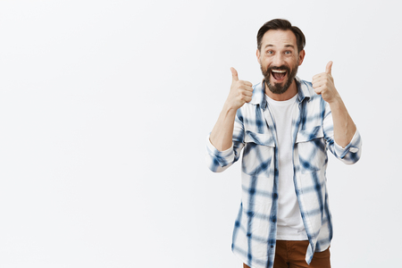 Yes I support you. Portrait of friendly and excited supportive father in casual checked shirt, raising thumbs up and smiling broadly while liking idea or cheering, accepting great plan over grey wall