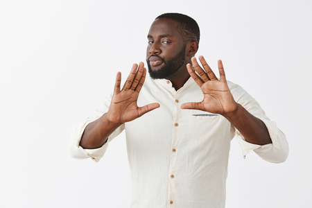 Easy man I got it. Serious-looking calm and confident professional African American businessman in white shirt raising palms near chest and gazing with self-assured expression at camera, calming down