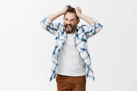 You make me man. Portrait of stressed intense and bothered crazy bearded man, pulling hair out of head and screaming from anger and negative emotions, yelling, being pissed and fed up of everything Stock Photo