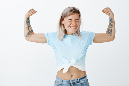 Girl power is strongest. Portrait of joyful good-looking active sportswomen with fair hair and tattooed arms, showing muscles or biceps, smiling broadly with closed eyes, being strong and confident Imagens