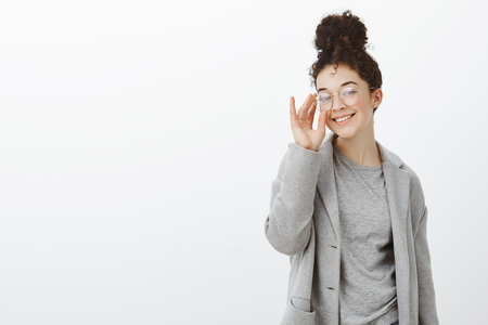 Indoor shot of self-assured good-looking woman with curly hair in gray coat and glasses, touching rim of eyewear while smiling joyfully at camera, being pleased and satisfied over gray background