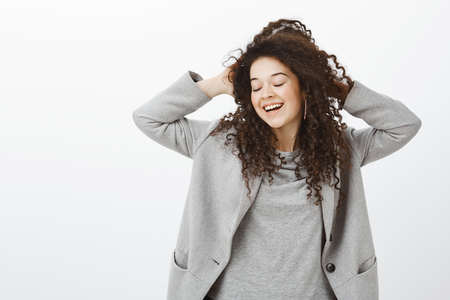 Enjoying life to fullest. Happy feminine dreamy girl with curly hair, closing eyes, touching head, smiling joyfully, expressing tender and timid attitude, feeling carefree and relieved over gray wall
