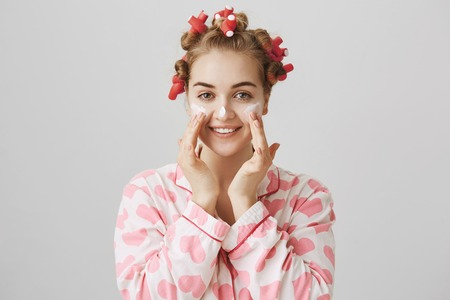 Attractive blonde caucasian model in hair-curlers, applying cream or mask on cheeks and nose, rubbing it with hands and smiling, taking care of face before going out. Skincare and beauty concept