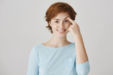 Girl can not lift her eyebrow without help of hand. Portrait of happy attractive redhead female student with freckles in ordinary clothes pulling brow with index finger, smiling and being in good mood