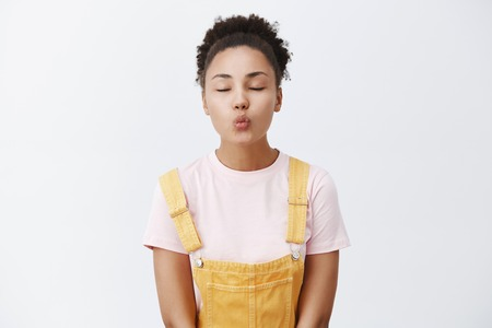 Girlfriend came home, waiting near porch for boyfriend kiss her. Cute African American female in yellow dungarees, folding lips to give mwah, closing eyes, standing passionately over gray background Archivio Fotografico