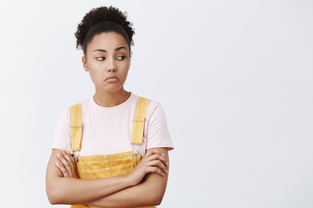 Not bad, nice shoes, want them too. Confident cool African American woman in yellow overalls, pursing lips and gazing right, holding hands crossed on chest, liking something, checking it out Imagens