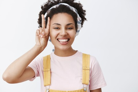 Make peace do not stress. Portrait of carefree charming and relaxed African American female in yellow overalls and headband showing victory gesture near face and smiling proud and happy 免版税图像