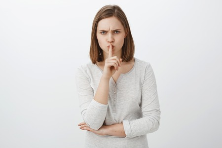 Keep mouth shut I prohibit tell anyone my secret. Portrait of serious-looking irritated bossy girl with brown hair frowning shushing at camera with index finger over mouth demanding keep quiet Stock Photo