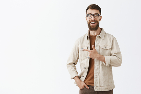 Gosh look how amazing. Portrait of impressed enthusiastic hipster guy with long beard and short hairstyle in black glasses smiling admired pointing left being astonished over gray background Imagens - 107016077