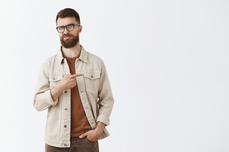 Indifferent displeased adult european male entrepreneur in beige jacket over brown t-shirt and glasses with sick long hipset beard pointing right frowning from scorn and disdain, unimpressed disliking