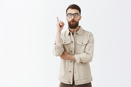 Studio shot of man invanting great idea or plan in mind yelling eureka with raised index finger and thoughtful excited look having suggestion sharing with team thoughts over gray background Stock Photo