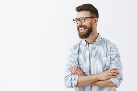 Creative happy and funny bearded man with moustache in glasses with black rim turning left laughing out loud enjoying interesting and hilarious conversation holding hands crossed on chest relaxed