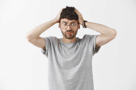 Mind of man blowing from troubles. Frustrated intense funny and handsome young male with beard in glasses pursing lips holding hands on head and gazing at lower right corner with panic and anxiety