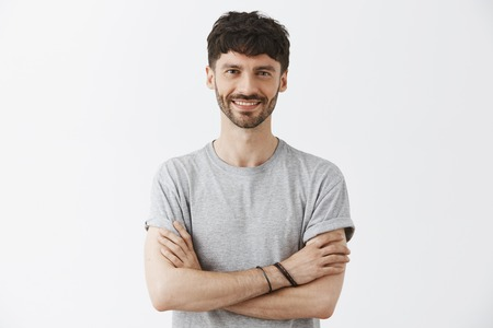 Waist-up shot of confident good-looking mature european male entrepreneur in t-shirt holding hands crossed in self-assured pose and smiling with assured pleasant smile over gray background Фото со стока