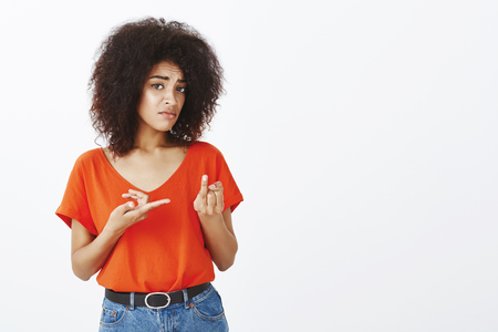 Excuse me, where is ring. Displeased questioned charming african woman with afro haircut, sticking out finger and pointing with another hand, wanting get married, asking boyfriend about marriage Standard-Bild - 107302531