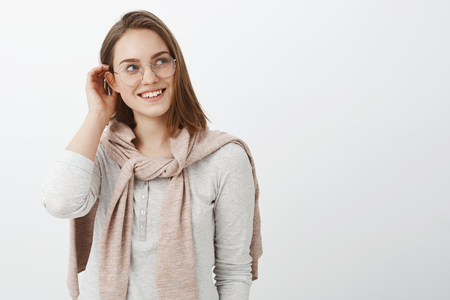 Waist-up shot of feminine creative and charming young girl in glasses and pullover knitten on neck putting hair strand behind ear and gazing charmed and tender to right with cute smile