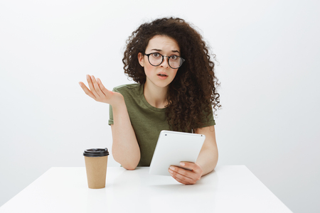 Studio shot of clueless confused charming woman with curly hair in eyewear, raising hand in questioned gesture, sitting at table, drinking coffee and holding white digital tablet over gray background 写真素材 - 107302908