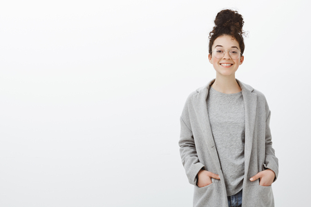 Portrait of confident happy good-looking girl with curly hair combed in bun, wearing gray coat and glasses, holding hands in pockets and smiling cheerfully at camera, feeling awesome over gray wall Фото со стока