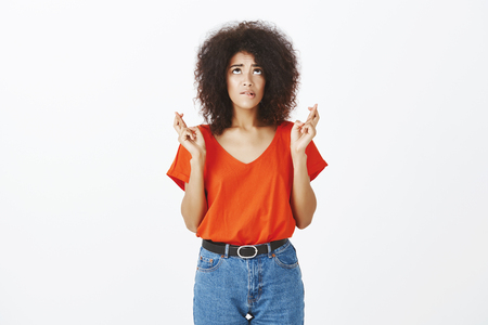 Indoor shot of intense worried female student with afro hairstyle, looking up and biting lip, standing with crossed fingers, begging or praying, making wish and wanting something badly