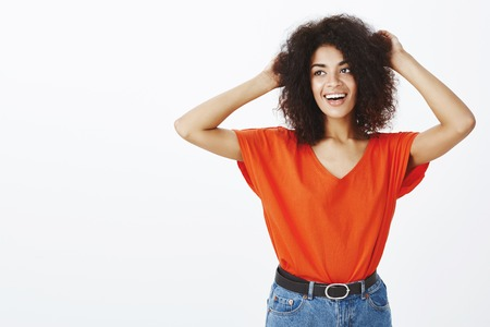 No worries, girl feeling carefree. Good-looking friendly female student with afro hairstyle, raising hands and touching head, gazing left with broad smile while standing in relaxed pose over gray wall