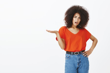What is your point, man. Questioned disappointed attractive dark-skinned woman with afro hairstyle, frowning, spreading hand in clueless gesture, asking question, being displeased with result