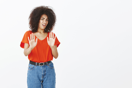 Gosh, take it away disgusting. Portrait of displeased unhappy african american woman with curly hairstyle, frowning, pulling hands in rejection and dislike gesture, expressing antipathy over grey wall 版權商用圖片